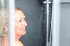 Smiling attractive senior woman taking a shower Royalty Free Stock Photos