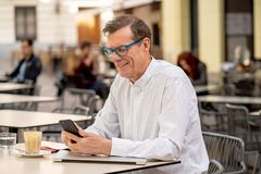 Smiling attractive stylish mature man using smart phone checking online sitting outside coffee shop royalty free stock image