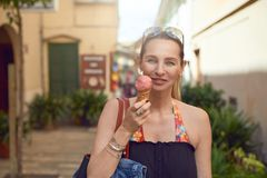 Smiling attractive stylish woman enjoying ice cream. Smiling attractive stylish woman with her sunglasses on her forehead enjoying an ice cream in a cone stock images
