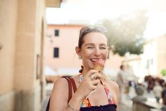 Smiling attractive stylish woman enjoying ice cream. Smiling attractive stylish woman with her sunglasses on her forehead enjoying an ice cream in a cone royalty free stock photos