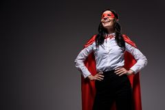 Smiling attractive super businesswoman in red cape and mask. Isolated on black stock photo