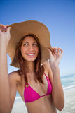 Smiling attractive teenager holding her hat brim in front of the. Smiling attractive teenager holding her hat brim while standing on the beach stock photography