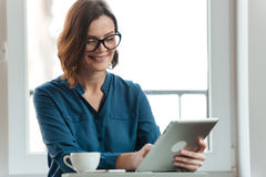 Smiling attractive woman in eyeglasses using tablet Stock Image
