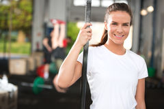 Smiling and attractive woman at fitness center. Fit young and happy woman rests after workout at a fitness gym center. People workout in the background Stock Photography