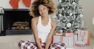 Smiling attractive woman in front of the Xmas tree Royalty Free Stock Photos