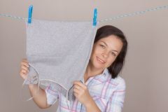 Smiling Attractive Woman Hanging Wet Clean Cloth To Dry On Cloth. Es Line At Laundry Room on a grey background Stock Photo