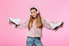 Attractive woman holding ice skates. Smiling attractive woman holding ice skates and listens to music on headphones Royalty Free Stock Photo