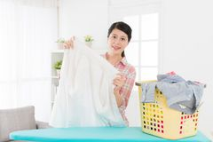 Smiling attractive woman holding white shirt. Checking clean and looking at camera when she folding clothing at home in living room Royalty Free Stock Photo