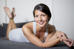 Smiling attractive woman on lounge sofa Stock Photos