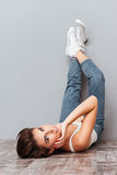 Smiling attractive woman lying on the floor with raised legs Royalty Free Stock Photography