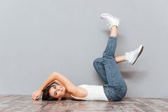 Smiling attractive woman lying on the floor with raised legs Stock Photos