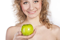 Smiling attractive woman offers a green apple Stock Images