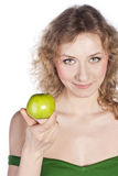 Smiling attractive woman offers a green apple Royalty Free Stock Photos