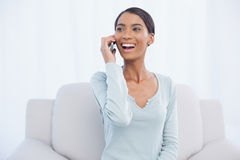 Smiling attractive woman on the phone sitting on cosy sofa Royalty Free Stock Photo