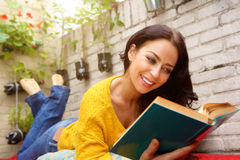 Smiling attractive woman reading book Stock Photography