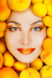Smiling attractive woman with ripe big fresh peaches and apricot Royalty Free Stock Photo