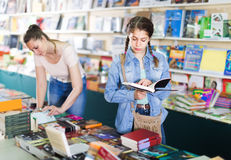 Smiling attractive woman showing open book to girl in book bouti Stock Photo