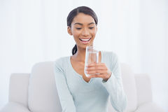 Smiling attractive woman sitting on cosy sofa drinking water Royalty Free Stock Photos