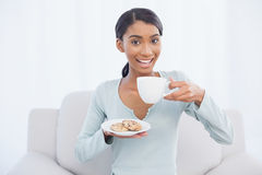 Smiling attractive woman sitting on cosy sofa holding coffee and Royalty Free Stock Images