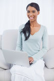 Smiling attractive woman using her laptop sitting on cosy sofa Royalty Free Stock Photography