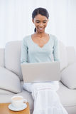 Smiling attractive woman using her laptop sitting on cosy sofa Stock Photos