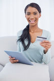 Smiling attractive woman using her tablet pc to buy online Royalty Free Stock Photo