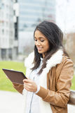 Smiling attractive woman using tablet computer in public space. Royalty Free Stock Photo