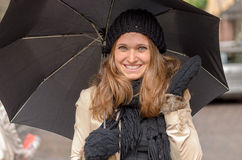 Smiling attractive woman in winter fashion. Wearing a knitted cap and gloves and holding an umbrella over her head as she stands in an urban street Royalty Free Stock Image