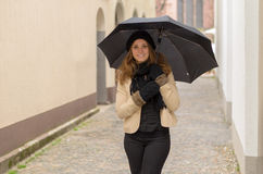 Smiling attractive woman in winter fashion. Wearing a knitted cap and gloves and holding an umbrella over her head as she stands in an urban street Royalty Free Stock Photos