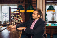 Smiling attractive young barman wiping glasses and talking to man in bar Royalty Free Stock Image