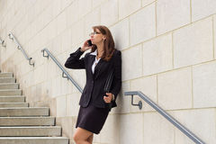 Smiling attractive young business woman executive talks on phone Royalty Free Stock Photography