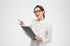 Smiling attractive young businesswoman holding clipboard and pointing away Stock Images