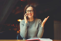 Smiling attractive young hipster girl having phone conversation Royalty Free Stock Images