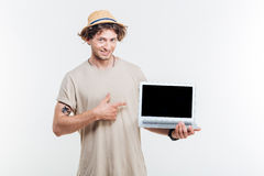 Smiling attractive young man holding blank screen laptop and pointing Stock Photo