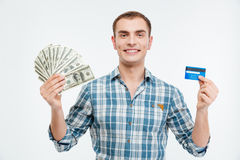 Smiling attractive young man holding cash and credit card Stock Photos