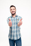 Smiling attractive young man showing thumbs up with both hands Stock Photos