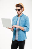 Smiling attractive young man standing and using laptop Stock Photos