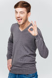 Smiling attractive young man winking and showing ok sign Royalty Free Stock Image