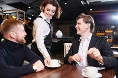 Smiling waitress serving tea to businessmen royalty free stock photo