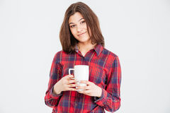 Smiling attractive young woman in checkered shirt with white cup Stock Photography