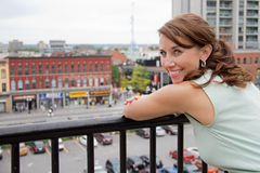 Smiling attractive young woman with city background looking at c Royalty Free Stock Photo
