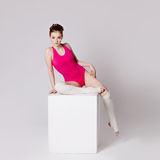 Smiling attractive young woman gymnast on a white Royalty Free Stock Images