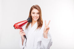 Smiling attractive young woman with hair dryer  showing victory sign Stock Image