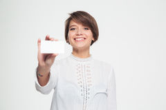 Smiling attractive young woman holding blank credit card Royalty Free Stock Images