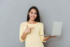 Smiling attractive young woman holding and pointing on laptop Stock Photo