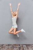 Smiling attractive young woman jumping and celebrating success Stock Photography