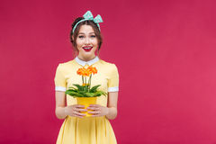 Smiling attractive young woman standin and holding flower in pot Stock Images
