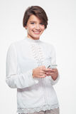 Smiling attractive young woman standing and using mobile phone Stock Photo