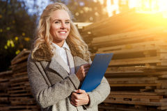 Smiling attractive young woman at work, inspector inspects wooden boards Stock Photos