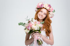 Smiling attractive young woman in wreath holding bouquet of flowers Royalty Free Stock Photography
